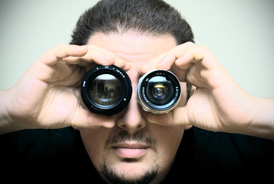 Man looking through lenses